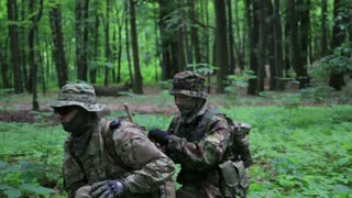 Guerilla warriors squad cover each other in forest carrying their guns. War battlefield maneuvers training
