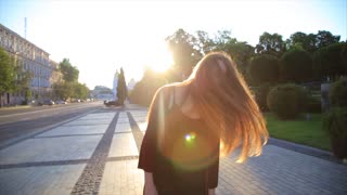Happy girl with long hair having fun outdoor in the city at sunrise. Beauty woman spinning, jumping and laughing. Freedom. Slow motion video footage