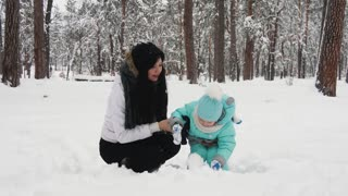 Happy woman and child playing with snow in winter park. Holidays in slow motion
