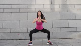 Happy young brunette fitness woman athlete making workout outdoors in the city on urban background in slow motion