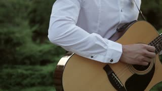 Hipster man play the guitar and sings outdoor by picturesque sunset and green background
