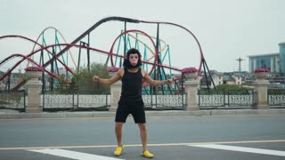 Hispanic man in monkey mask silly dancing in front of colorful roller coaster in amusement park with blue sky as background. Copyspace text.