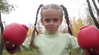 Little girl kid kicks boxing gloves one another making funny silly faces