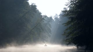 Lonely man with a paddle in the boat swimming on a calm river in dawn fog. The first rays of the morning sun make their way through the branches of trees