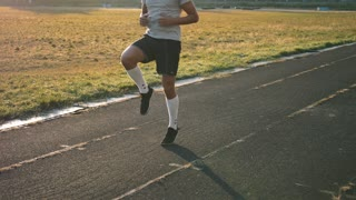 Mixed race athlete runner does high knees, while running in place at stadium in slow motion