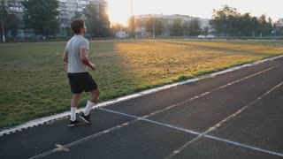 Mixed race athlete running on an all-weather running track alone. Sportsman runner sprinting on a black rubberized running track in slow motion