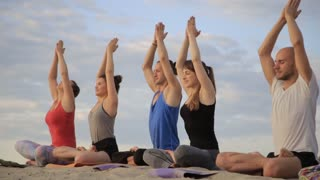 Mixed race group of people exercising yoga healthy lifestyle fitness warrior poses. Concentration