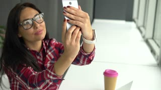 Mixed race young hipster woman with amazing smile wearing eclectic modern outfit makes selfie with coffee while sitting indoors in cafe