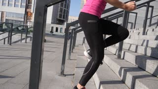 Outdoor close up shot of fit young woman running up stairs. Female athlete climbing up the steps. Steadicam slow motion close up shot.