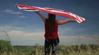 Proud american girl holding stars and stripes in slow motion. Patriotism concept