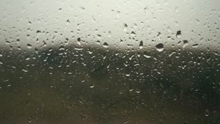 Rain drops appearing on a window glass, rain starting, droplets background.