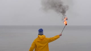 Rear view of man with fire torch in yellow coat on background of frozen sea. Snow falling in foreground