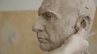 Sculptor modelling sculpture adjusting face details head made of clay. Creative concept