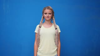Serious blond hipster student woman looking at camera over blue background.