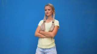 Serious blond hipster student woman looking at camera with arms crossed over blue background.