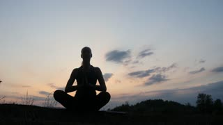 Silhouette young woman practicing yoga at sunset 4k