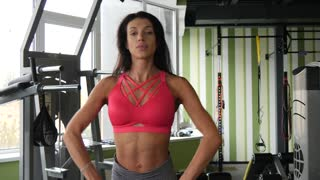 Slender mixed race female bodybuilder doing exercise with heavy weight bar. Close up of fitness woman practicing heabyweight lift at health club