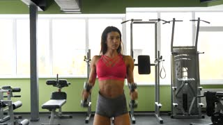 Slender mixed race woman exercising with weights in gym in slow motion