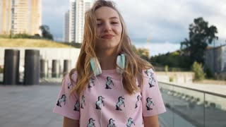 Slow Motion Portrait of Attractive Cute Smiling Caucasian Ethnicity Young Woman with Headphones and Backpack in Urban Environment. Millenial Hipster New Generation Y.