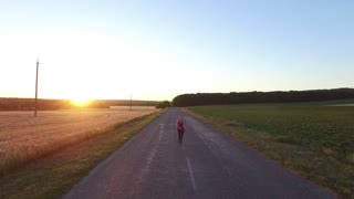 Sports jogger woman running a road near field at sunset. Health lifestyle concept