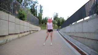 Steadicam shot of mixed race trendy hipster teenage girl walking wearing pink wig