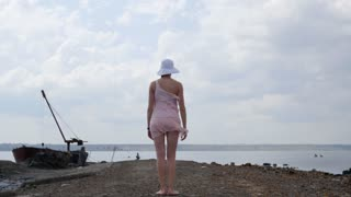 Tourist woman in beautiful dress walking to horizon. Travel experience at sunset, girl enjoying relaxed lifestyle on summer vacation 4k