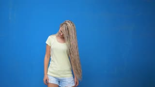 Trendy hipster girl shaking her braided hair pigtails and spinning around on blue background.