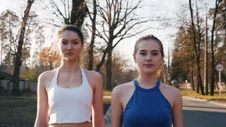 Two athletic woman running outdoors in slow motion on concrete track in park. Healthy fitness concept.