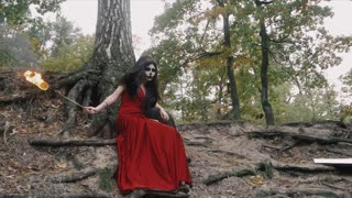 Two women with scary halloween make up in red and black dress sitting near tree in the forest park outdoors holding fire torch in hand. Steadicam slow motion shot