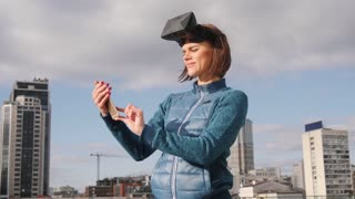 Virtual reality Girl uses vr head mounted display when texting sms or recieving call on phone. Slow motion