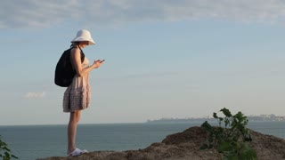 woman tourist is looking for a root with a GPS navigator on a smartphone, finds the way. Ocean sea beach at sunset