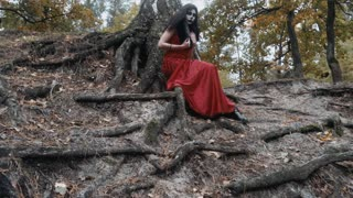 Woman with scary halloween make up in red dress sitting near tree in the forest park outdoors. Slow motion steadicam shot