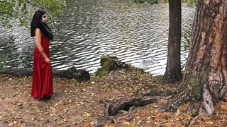 Woman with scary halloween make up in red dress walking in the forest park beetween the trees. Slow motion