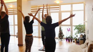 Yoga class of different age people exercising healthy lifestyle in fitness studio yoga with instructor. Slow motion