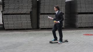 Young attractive business man office worker riding skateboard to work. Drinking latte coffee and talking on the phone. Mixed race latin hispanic ethnicity. Slow motion steadicam shot