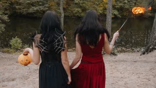 Young halloween girl friends in black and red witch dress having fun in the forest park with traditional autumn holiday symbol of orange spooky pumpkin outdoor