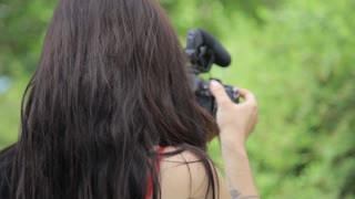 Young mixed race female indie film maker shooting in a green natural setting with grass on background. DSLR camera with microphone
