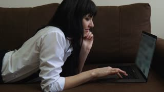 Young pretty woman using laptop. Smiling girl sitting on sofa relaxing while browsing online shopping website on laptop. Happy girl browsing through the internet during free time at home.