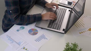 Young woman finance market analyst working at office on laptop while sitting at wooden table. Businessman analyze finance charts. Graphs and diagramms