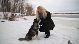 Winter landscape with blonde girl playing with siberian husky malamute dogs outside. Forest, beach, frozen river.
