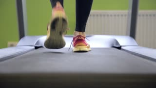 Woman run on a treadmill. Close-up legs shot. Running on a walking machine. Healthy lifestyle concept.