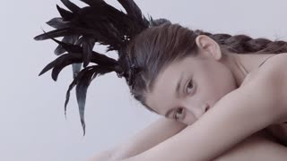 Young mixed race caucasian woman vogue portrait with feather mohawk accessory wearing black bodysuit sitting on wooden floor on white wall background. Fashion concept