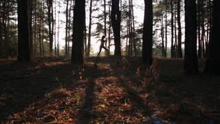 Young woman doing kick box exercise, expressing aggression. Fighting alone in serene forest at sunset