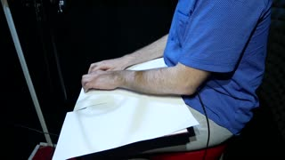 Blind Man in Black Glasses and Blue Shirt Reads Braille from White Paper Sheet and Recording Voice or Song in the Sound Recording Studio For Cartoon, Movie or Promotional Movie
