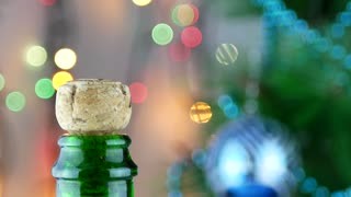 Champagne explosion. Man's hand opening champagne bottle closeup. Sparkling wine over holiday bokeh blinking background. Champagne bottle closeup. Success celebrating
