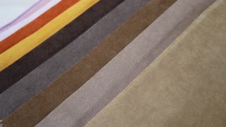 Fabric Samples Of Different Colors In Move Are Spinning And Rotation: White, Orange, Yellow, Brown, Gray. Textile Textures Fabric Swatches