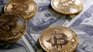 Gold Bit Coin BTC coins rotating on bills of 100 dollars. Worldwide virtual internet cryptocurrency and digital payment system. Digital coin money crypto currency on bitcoin farm in digital cyberspace