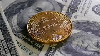 Gold Bitcoin BTC coins are falling on bills 100 dollars. Digital coin money crypto currency on bitcoin farm in digital cyberspace. Worldwide virtual internet cryptocurrency and digital payment system