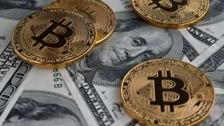 Gold Bitcoin BTC coins rotating on bills of 100 dollars. Digital coin money crypto currency on bitcoin farm in digital cyberspace. Worldwide virtual internet cryptocurrency and digital payment system