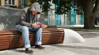 Hooded man holding red smartphone and credit or debit card and buy online outside near tree on a brown bench